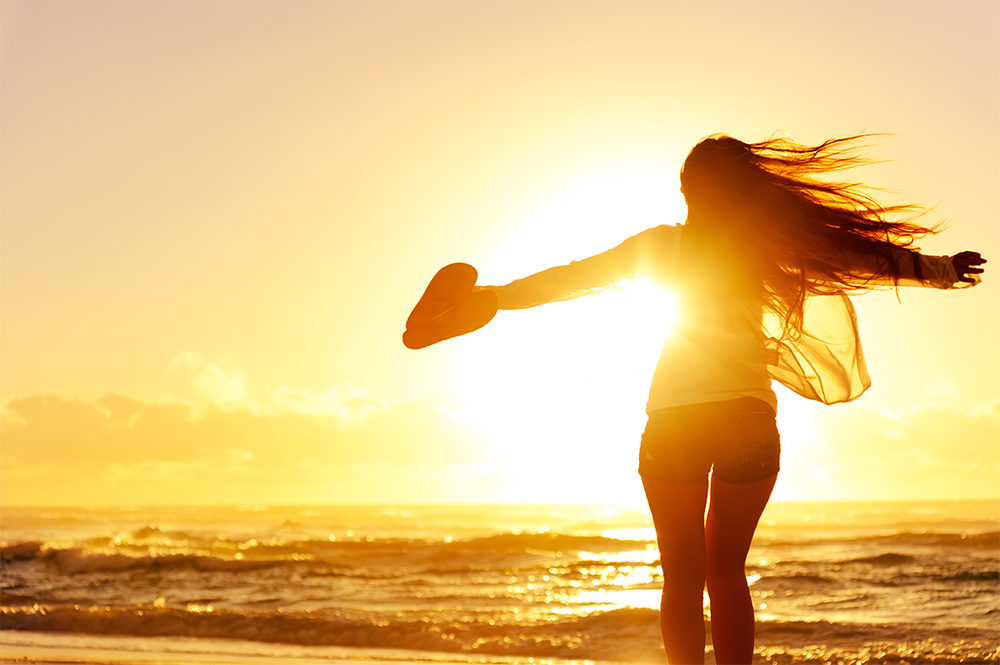 healthy and happy woman at sunset how to balance your hormones naturally