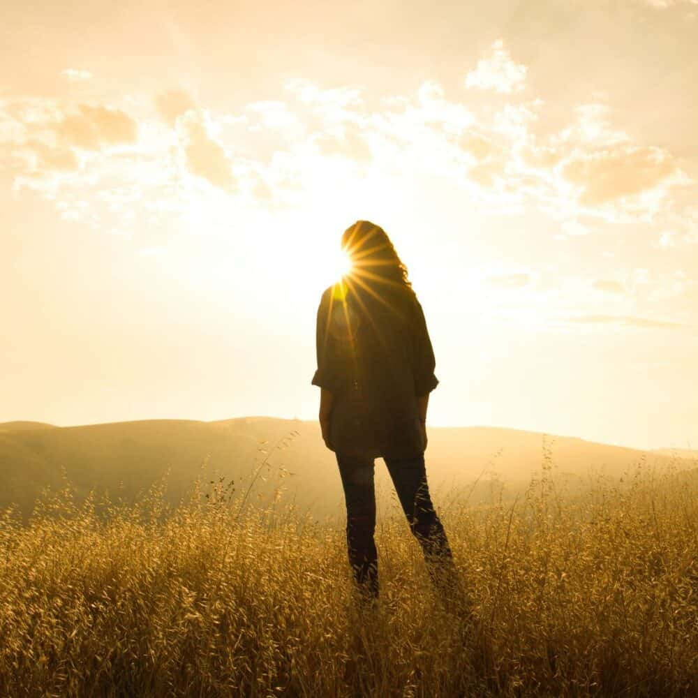 Woman in cornfield with sun